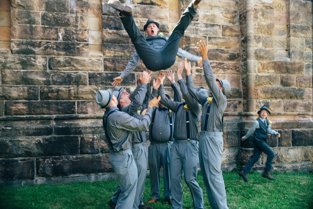 Groomsmen throwing groom up in the air in a basket toss while ring bearer runs away