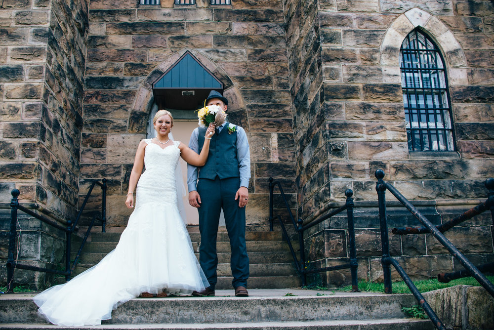 Bride smacking groom in the face with bouquet at Old Cambria County Jail in Ebensburg, PA