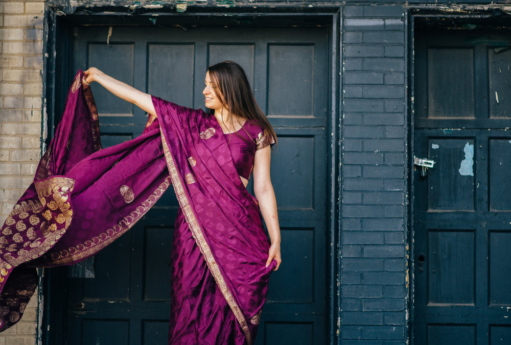 purple and gold Indian sari floating in the breeze worn by model in front of a black garage door in an urban setting
