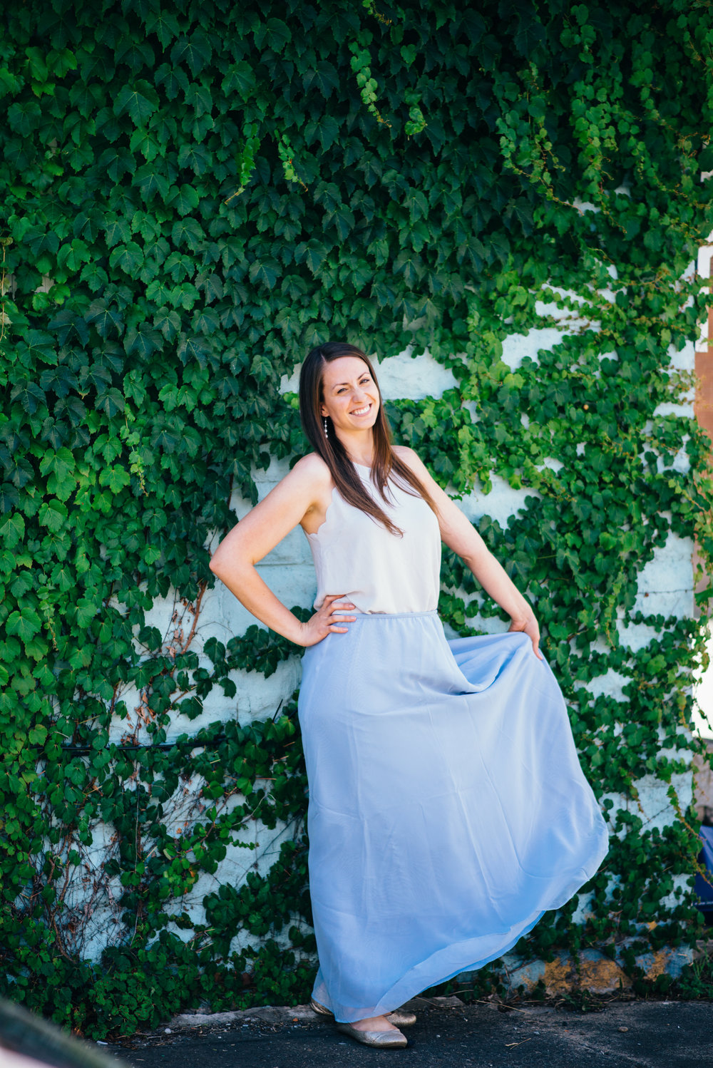 Bridesmaid in two piece bridesmaid dress with a periwinkle or sky blue skirt and grey spaghetti strap crop top standing in front of an ivy wall