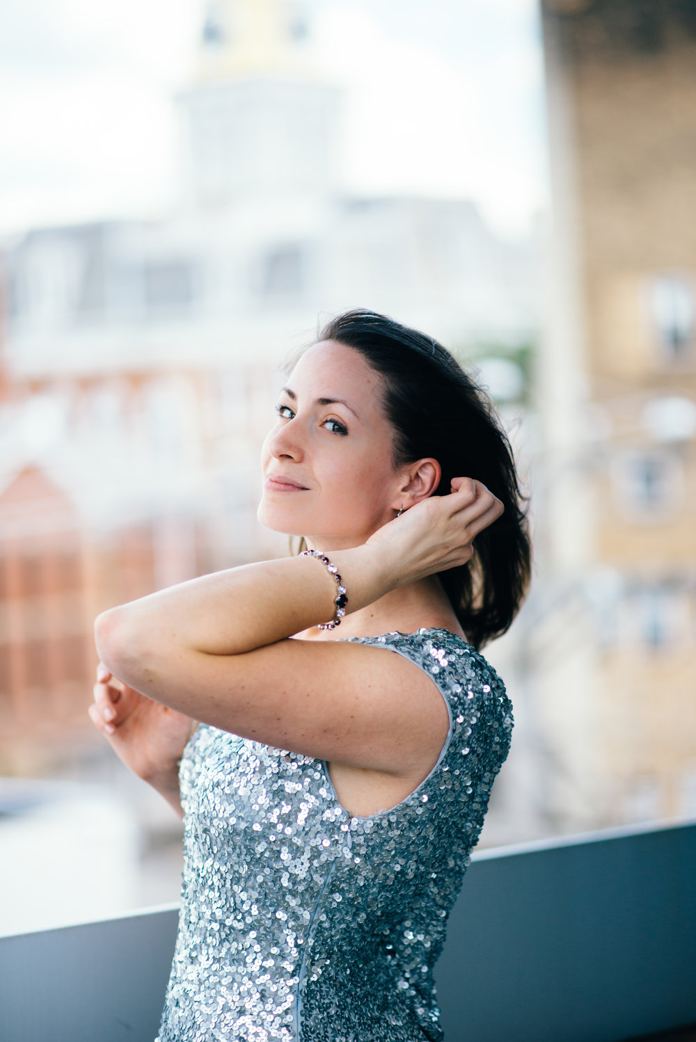 bridesmaid in a long silver sequin gown in front of city-scape