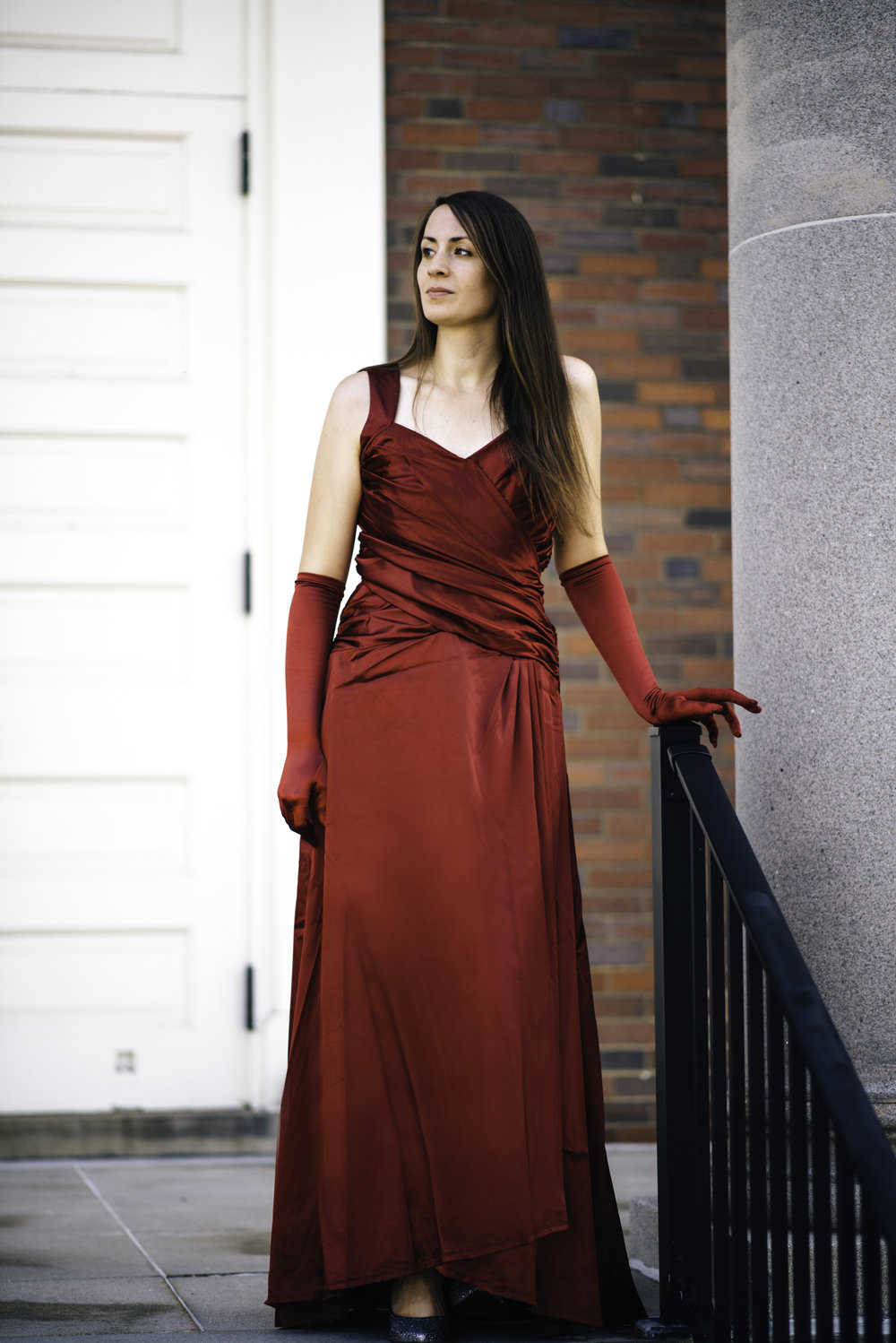Bridesmaid standing in front of white doors beside a column wearing crimson red satin floor length dress with red elbow length gloves