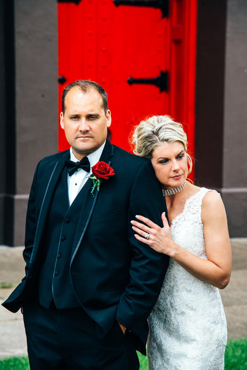 Bride and groom in front of bright red church door