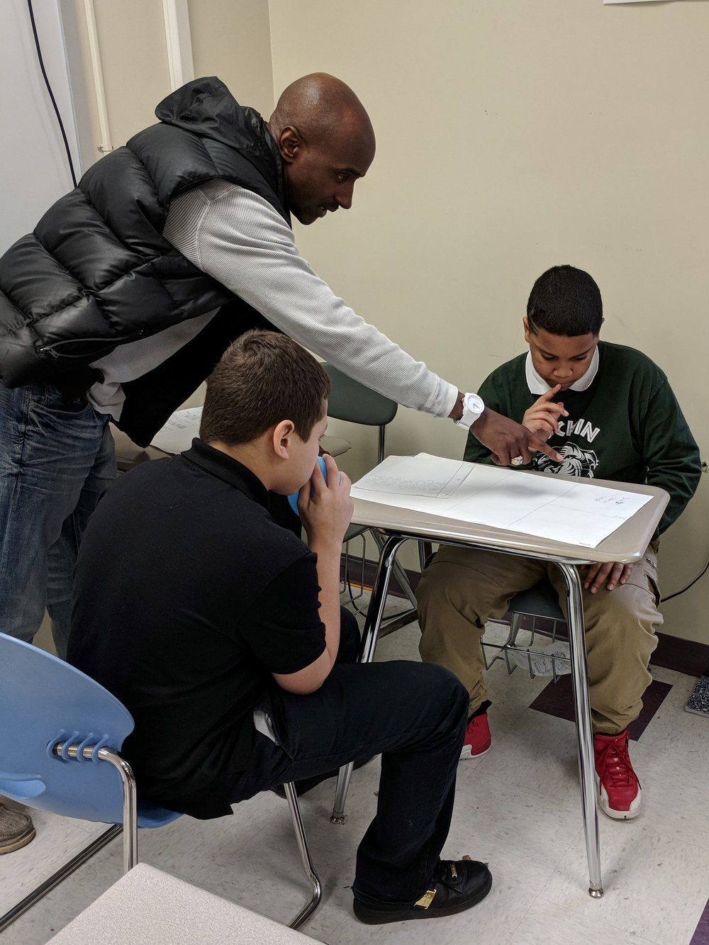 ABOVE : VP of HoodRISE Global Inc.; Dr. Gerald Jarmon, assisting some of HoodRISE Academy's 7th grade boys that are working on the storyboard phase of their '16-barz In The Classroom' project, at Rowland School in Harrisburg, PA.