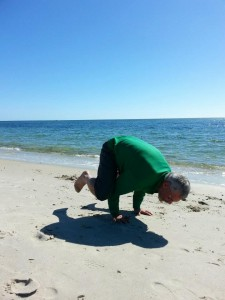 The author's dad, Yogaman Bill, letting go of anxiety and creating beauty on the beach.