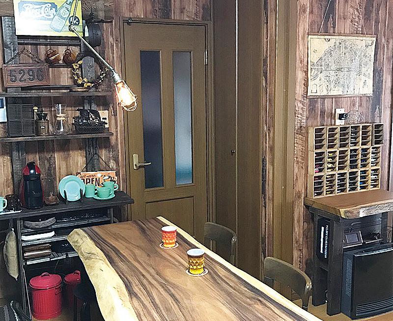 キッチンの壁にDIYでシェルフを設置。照明はエジソンバルブ、テーブルはモンキーポッドの一枚板。