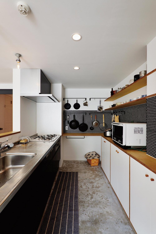 キッチンは作業場所が多いコの字型。壁の棚に好きな器を飾り、よく使う道具は吊るして収納。