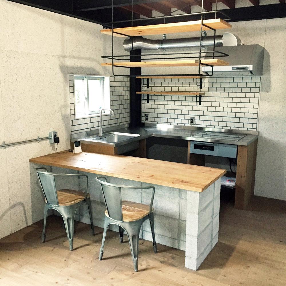 コンパクトなキッチンと吊り棚は造作。テーブルは4人向かい合って座れる。