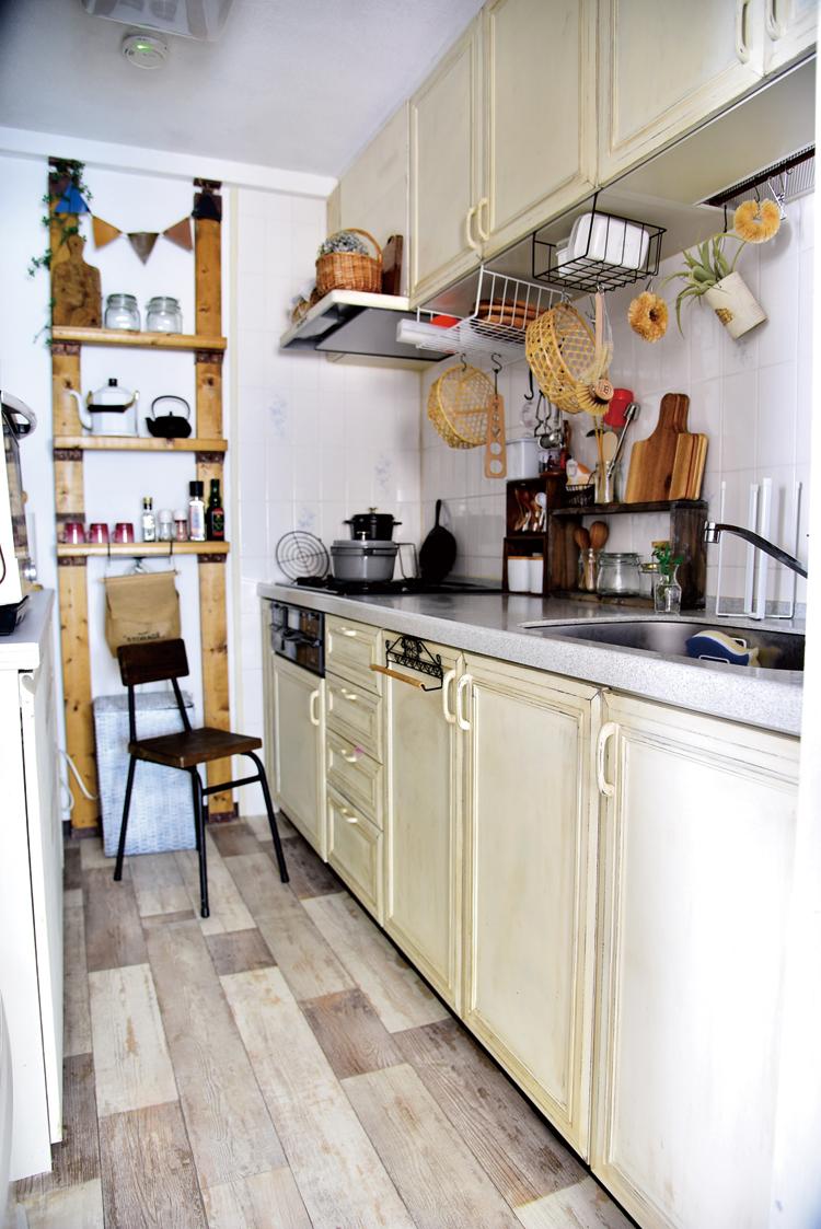 システムキッチンの扉を塗装してエイジング加工。床は古材風クッションフロアに変更。