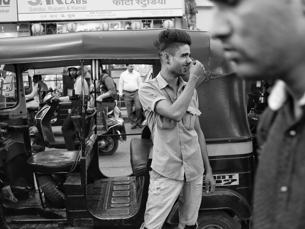 Okay, there's nothing to this photograph. It's a candid picture of an auto-rickshaw driver laughing on a joke made by another rickshaw driver. He had a cool haircut, though.