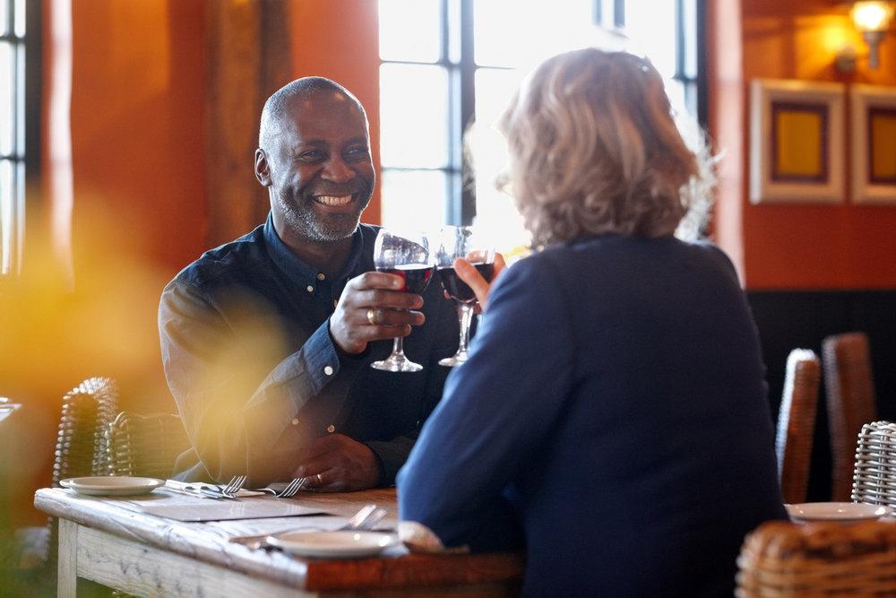 Happy-mature-couple-enjoying-wine-in-pub-472041945_1255x837.jpeg