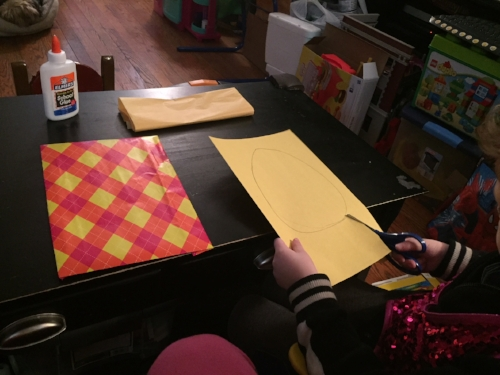 Cutting egg shape from yellow construction paper