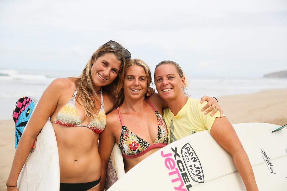three sisters with boards on beach.jpeg