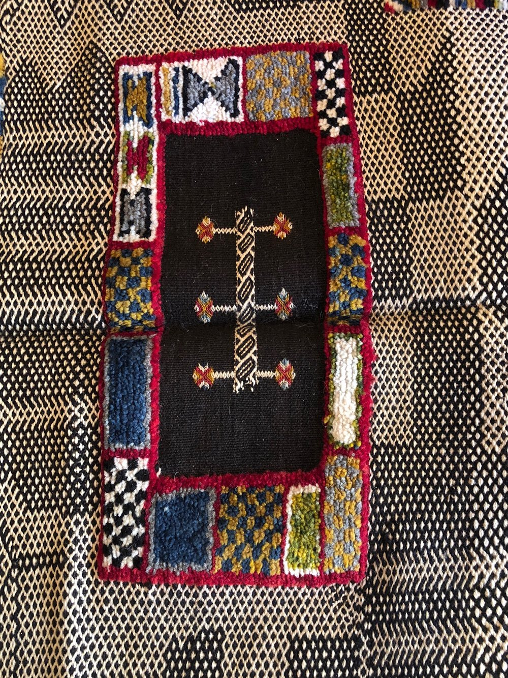 A traditional Berber symbol within the rug design.