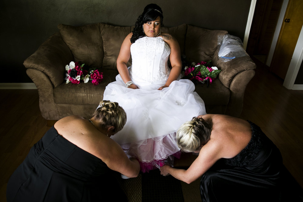 Lace Bellamy, 24, of Owensboro, Ky., sits in anticipation of her wedding day as her bridesmaids help her put on pink converse shoes.