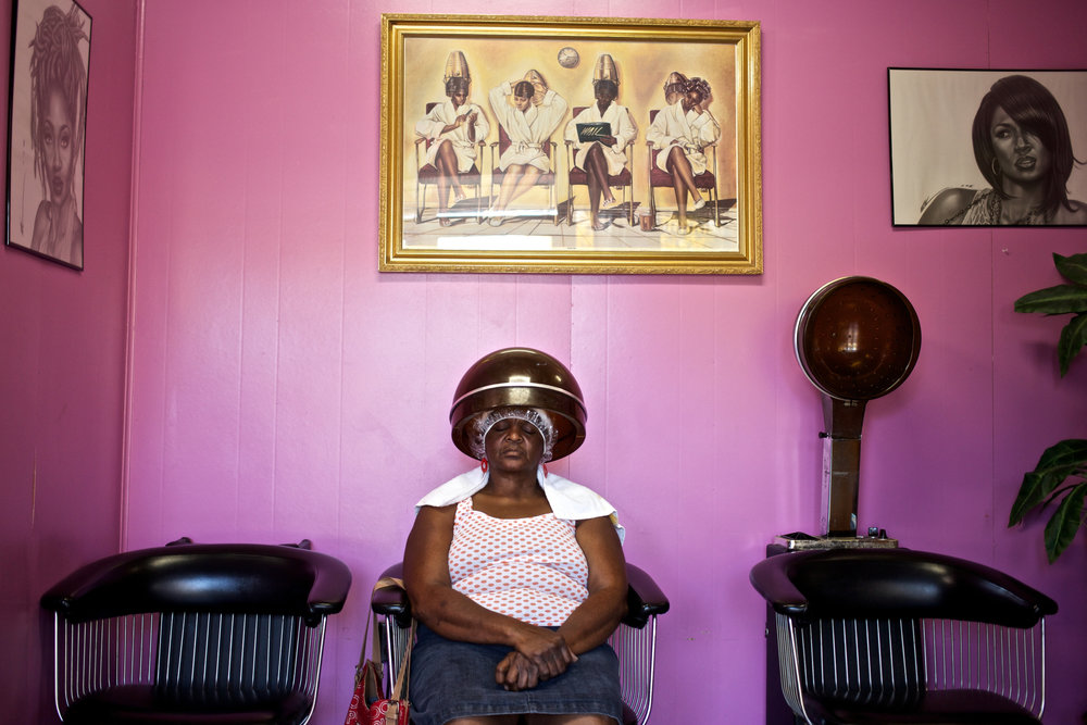 Referred to by the community as Ms. Ann, a regular at Shake Rag salon takes a nap under hair dryer as she receives a relaxing treatment on her hair. The salon was one of the few businesses remaining stable in the historic Shake Rag District of Bowling Green, Ky. As of October 2016, it was turned into a commercial loan office.