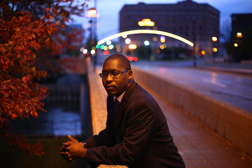 "Kayamone Sutton, 30, in downtown Flint, Mich., on October 23, 2016. A native of the city's north side, Sutton is running for Flint City Council in hopes of representing the 4th ward and bringing about positive political change.  ""I look at it from the standpoint of what do the people want,"" Sutton said. ""I think people want a candidate that is for the people, is actually going to help the people and tackle the issues, the real issues, and actually do what they say they're going to do when they get into office and thats one thing thats been lacking at the local level, all the way up to the federal level, even up to the presidency. So when it comes to voting, I'm not completely happy with the two choices that we have but I'll go for the lesser of the two evils which would be in my opinion, Hillary Clinton."" For  The Ground-Truth Project."