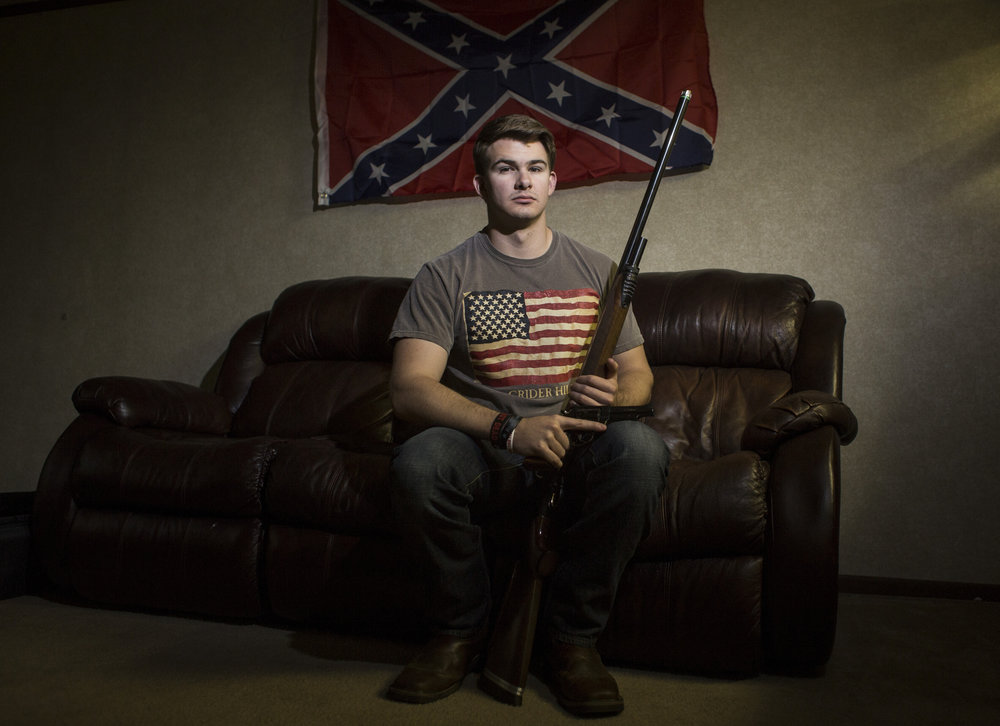 "Bowling Green, Kentucky: Greg Wellman, 21, of Greenup County, Ky., sits in his living room with two of the three firearms that he has at his residence. ""I think if you got your concealed and carry you should be able to carry. I've been shooting since I was old enough to hold a gun and my father has been shooting since he was a child. I grew up with it and all of my family is pro-gun,"" Wellman said."
