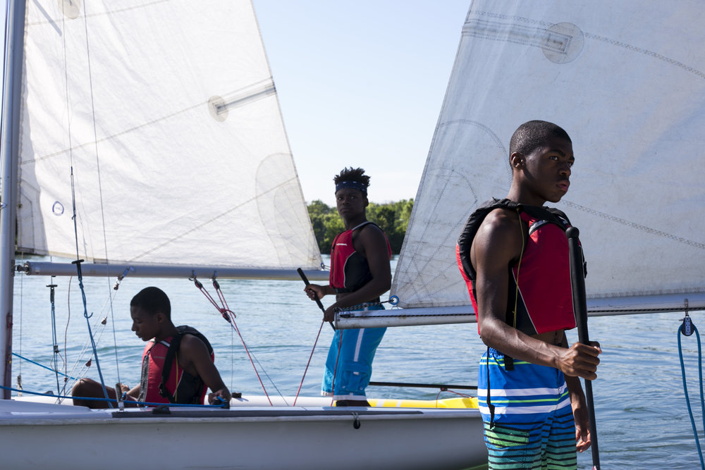 From left to right, Jacob Wooten, 14, Abdullah Bayi, 14, and Jaden Walton, 12, listen to instructions from an instructor before going out on the water during a junior sailing program for Detroit youth at the Detroit Yacht Club on Tuesday, August 1, 2017