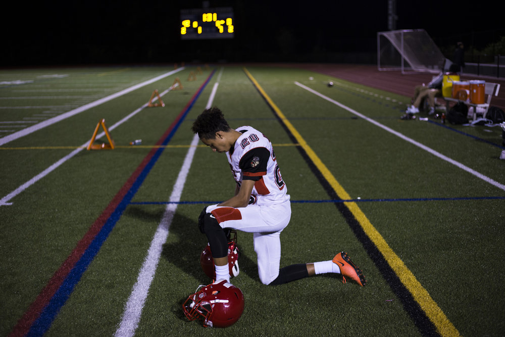 Wide receiver, David Porche Mayes, of the High School of Commerce kneels as he waits for the clock to run out as his team faces a 0-42 half-time score during a game in West Springfield, Mass., on Friday, September, 8, 2017.