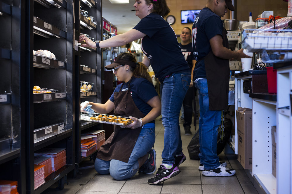 Jennilease Gomez, 17, shifts trays of donuts at the Dunkin Donuts where she works on the weekends in South Hadley, Mass., on Saturday, September, 10, 2017. Gomez said she originally got the job in order to help support her brother, 11, and 7, as her mother has a hearing disability which holds her back from working. This year she bought her siblings school clothes.