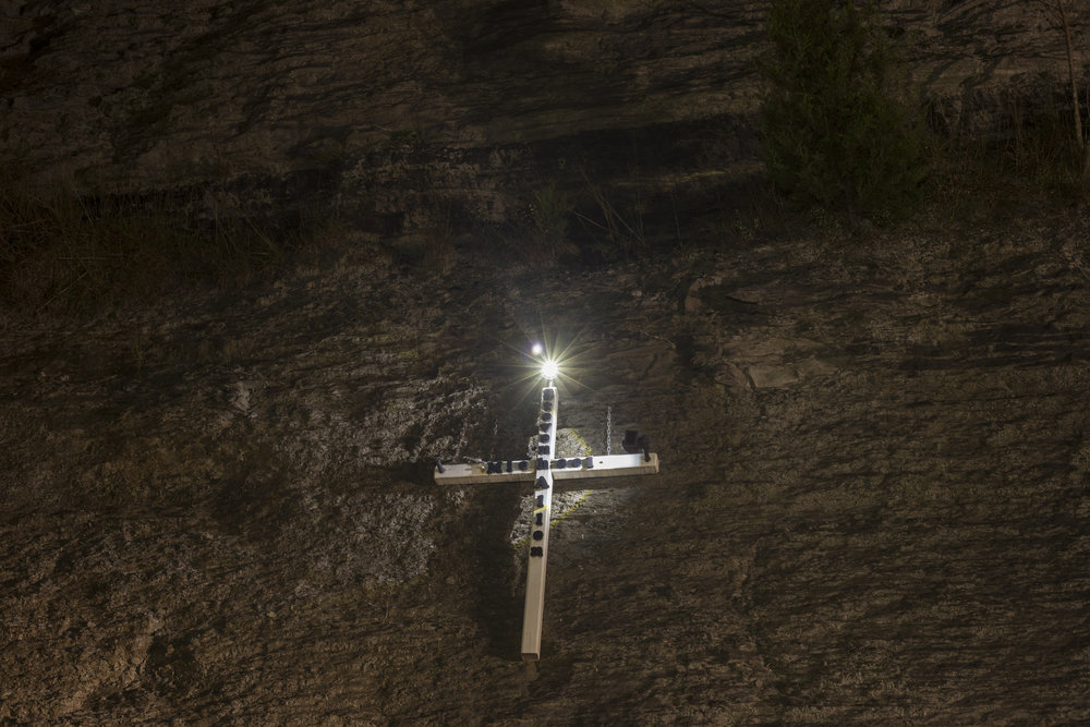 A cross in honor of a man named Steven Michael Allen is nailed into a wall of rock along I-23 near Tram, Ky., on Sunday, September 23, 2017.