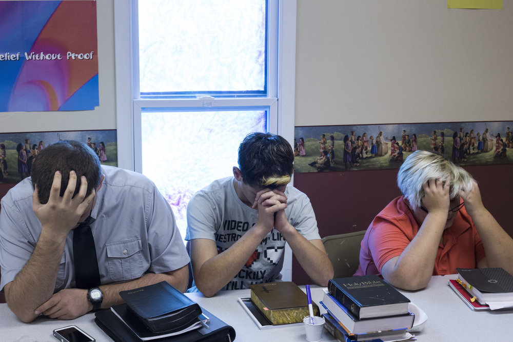 Students bow their heads to pray during Sunday school at the First Baptist Church in McDowell, Ky., on Sunday, September 24, 2017.