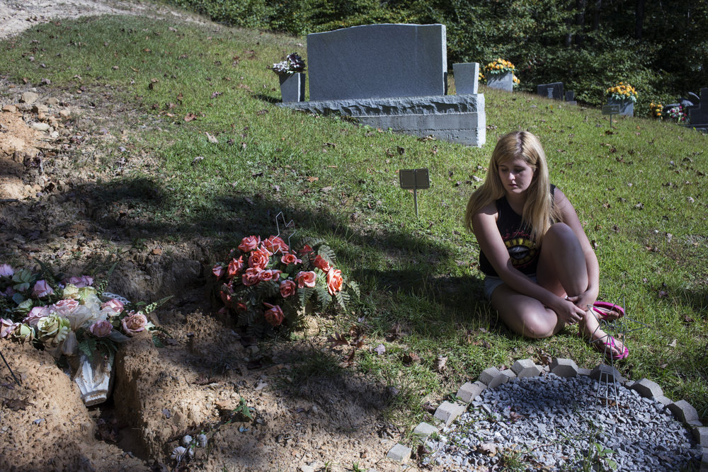 Lizzie Jones visits the grave of her parents in Belvinsville Ky., on Sunday, September 24, 2017. Jones said she likes to sit in silence when she visits with her parents as she feels like she's having an internal dialogue with them that is more spiritual than it is direct.