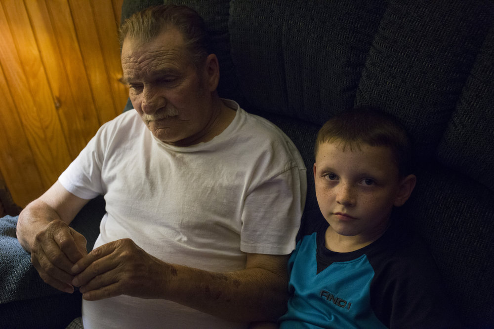 Chase Newman, 8, sits in a reclining chair with his grandfather Doff Justice as he watches TV at their home in Grethel Ky., on Thursday, September 28, 2017.