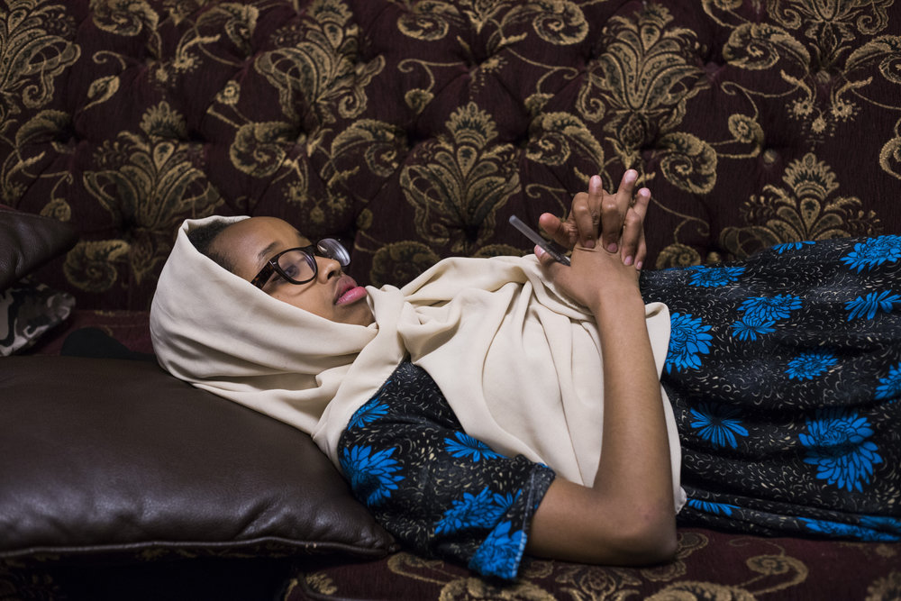 Aisha Mohamud, 13, lies on her couch as her mother Waris Mohamud, helps her little brother, Abdullah tell a classic Somali story at their home in Minneapolis, Minn., on Thursday, October 12, 2017.