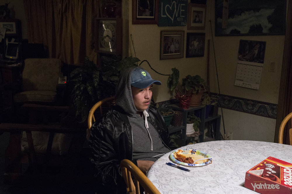Xavier Smith, 17, sits at the kitchen table in his grandmothers home as his grandmother, mother, his mother's boyfriend enjoy a card game, in Pablo, Montana., on Saturday, October 21, 2017.