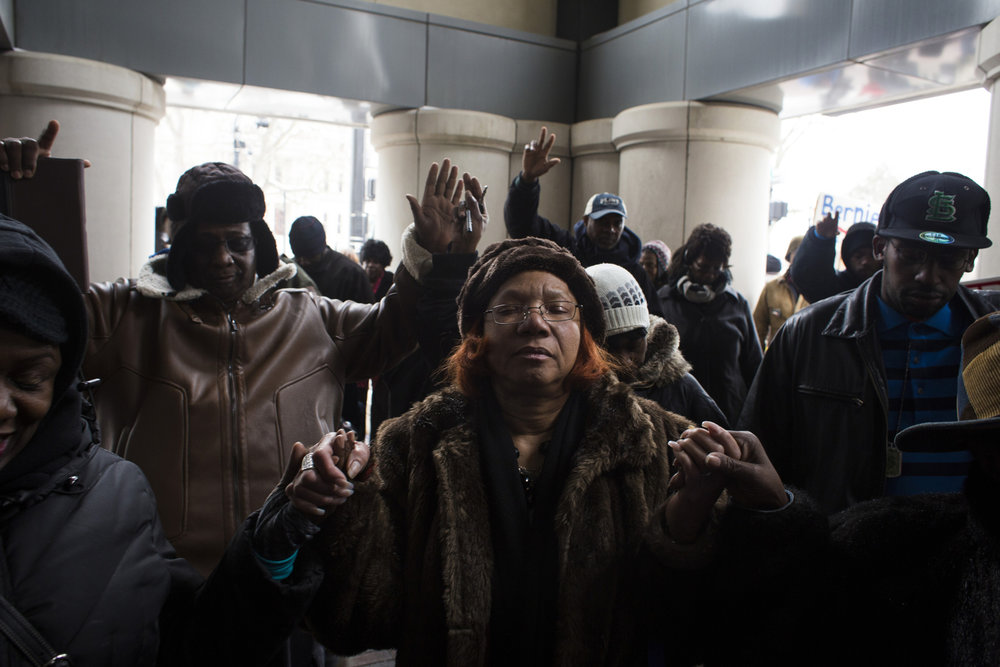 Earlene Love, 64, prays alongside her peers as protestors gather outside the Romney building, which houses the office of Governor Rick Snyder, in Lansing, Mich., on January 14, 2016. Earlier protestors had filled the front entrance of the building, conflicting with officers who said they would not be permitted inside. Throughout the city's water crisis, many residents have viewed Snyder as a distant leader whose priorities were never on Flint's well being.