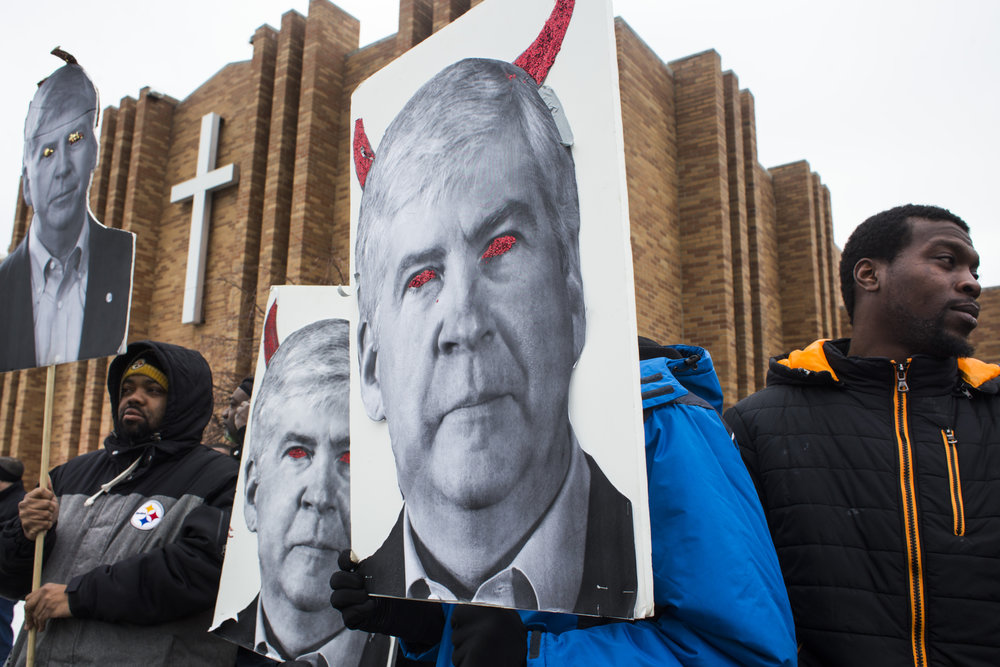 Protestors bear signs likening Michigan Governor Rick Snyder to the devil as they wait for a scheduled march to begin in front of the Metropolitan Baptist Tabernacle Church in Flint, Mich., on Friday, February 19, 2016.