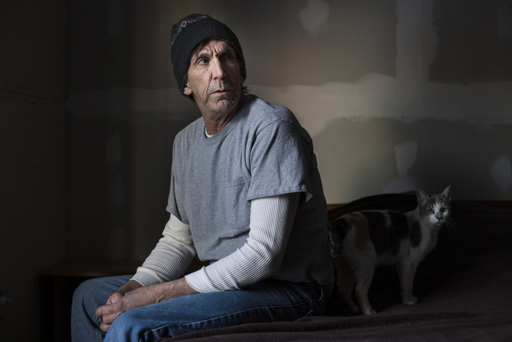 "Tim Monahan, 58, sits in his bedroom at his home in Flint, Mich., where he lives with his partner, on Saturday, February 13, 2016. Monahan was diagnosed with Legionnaires, a bacterial pneumonia, in July of 2014 and was one of the first cases amidst a Legionnaires spike in Genesee County following the switch to the Flint river as a water source months prior. ""They (city officials) knew what was going on and they didn't tell anyone,"" Monahan said. ""If the public had been told that here was a bacterial outbreak I don't know if you would have had eight or nine people die."""