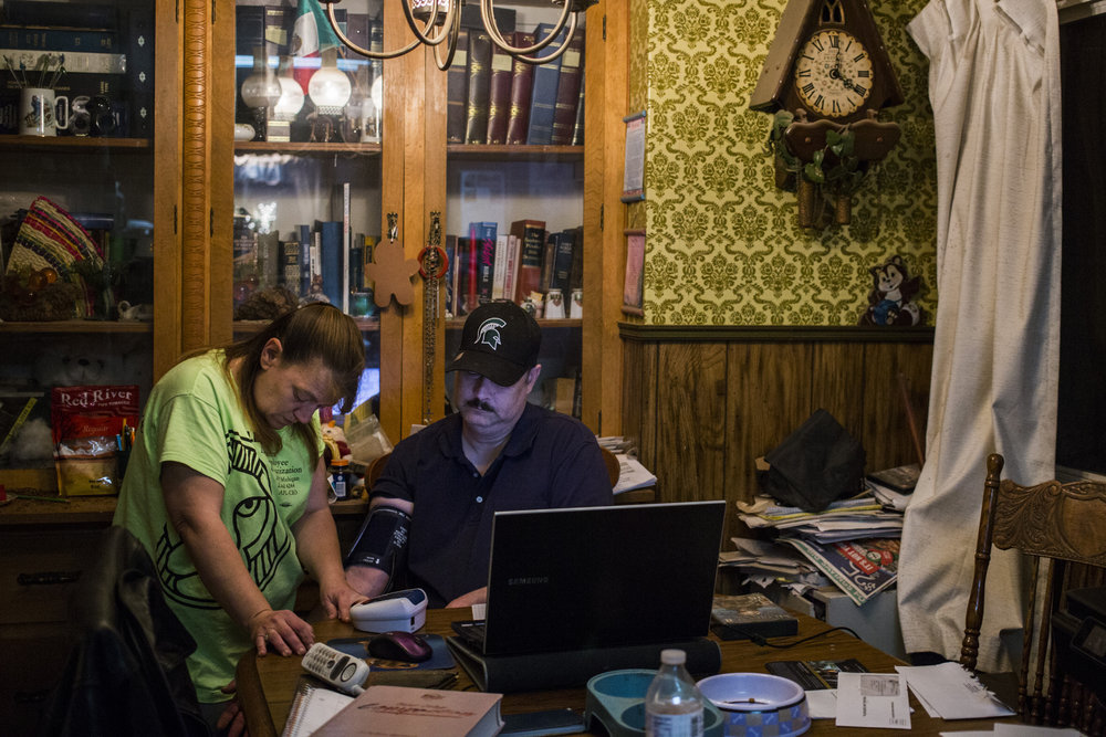 Keri Webber tests the blood pressure of her husband, Michael Webber, at their home in Flint on May 22, 2017. Just days before the reports of lead in the water went public, Keri's husband Michael suffered an eye stroke leaving him nearly blind in one eye. He said he now understands it to be a direct result of his skyrocketing blood pressure, a common symptom of lead poisoning in adults. All members of the Webber family have been diagnosed with lead poisoning.
