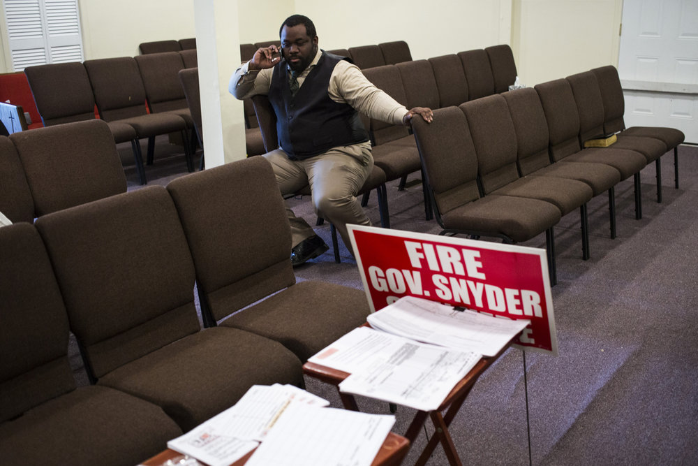 Julius Austin, 28, of Detroit, Mich., answers a call while working at the Due Season Family Life Center as part of efforts for Stop Snyder, a recent political startup calling for Governor Rick Snyder's resignation, in Flint, Mich., on April 20, 2016.