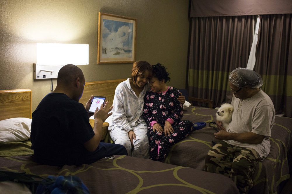Darline Long, 58, of Flint, Mich., embraces her daughter, Wendy Long, 36, as she and her family spend the evening at a Super 8 Motel in Burton, Mich., on April 9, 2016. Long and her family stayed at the motel specifically to bathe outside of the city of Flint. The family makes the trip only when they have the funds available and see it as an opportunity to bond over the trauma they've faced.