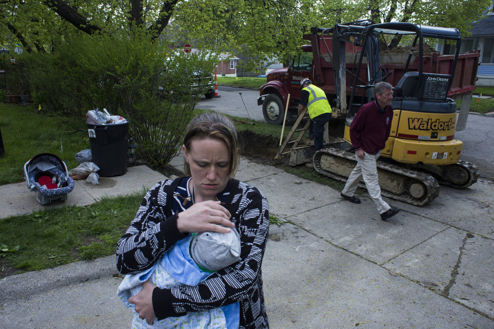 Christina Murphy, 35, of Flint, Mich., holds her newborn son, Declan Murphy, during a removal and replacement of a lead pipeline outside of their home on May, 7, 2016. Due to a disorganized construction grant that replaced the eroded pipes in the interior home, Christina and her family of five were displaced in hotel rooms for over three weeks. This was one of the few visits they were able to make to the home to oversee construction. According to mapping by the University of Michigan-Flint, there are over 4,000 known lead lines. Four years into the crisis, replacement efforts continue.