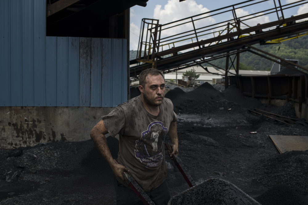 Jordan Noble, 23, moves a wheel barrel full of debris as he cleans the basement of the coal wash building at the NFC Mining coal processing site in Prestonsburg, Floyd County, Kentucky, on August 14, 2018.