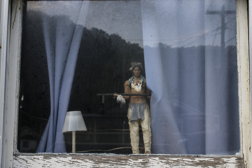 A small statue depicting a Native American sits in the window at a home in Wheelwright, Floyd County, Kentucky, on August 12, 2018.