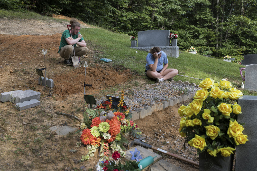 "Lizzie Jones, 18, and her boyfriend Dakota Berry, 20, take a break, both frustrated, while trying to fix up the gravesite of her parents at the Buckingham Cemetery in Buckingham, Floyd County, Kentucky, on August 9, 2018. Jones, who just graduated high school, is stressed about finding the money and time to fix up the grave sites in order to honor her parents.  ""It's so expensive to die. That's pitiful. It cost money to die,"" she said once she left the site. 