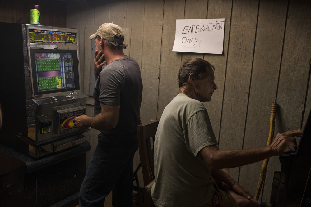 Locals play casino games in the back of the office space for B&L Construction, which is also a corner store, in Drift, Floyd County, Kentucky, on August 5, 2018.