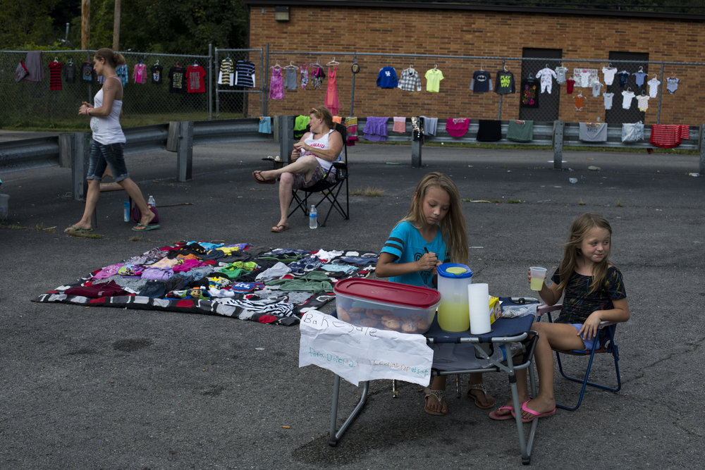 Natalie Deavers, left, 9 and her sister, Gabriella Deavers, right, 8, sell lemonade on the side of the highway as their mother, Mariah Miles, not pictured, joins friends to sell clothing and figurines as a way to bring in a source of income in Wheelwright, Floyd County, Kentucky, on August 12, 2018. Renee Pennington, one of the women selling clothing, said the options for employment are few and dwindling since the decline of the coal industry.