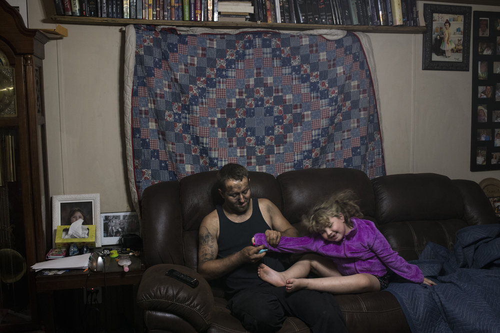 After a long shift at work, Thomas Jones, 27, tries to clip his 6 year old daughter's fingernails before her bedtime at their home in Eastern, Floyd County, Kentucky, on August 13, 2018. Jones is a fourth generation coal miner and recently received multiple certifications in computer science. Despite his education, he said he has found few positions open that are higher paying than the mines.