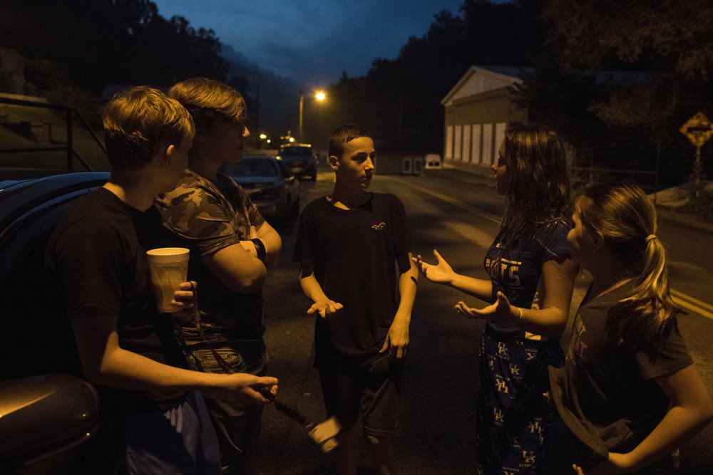 Brandon Slone, 13, jokes with friends as they hang out for the evening on the main street passing through Wheelwright, Floyd County, Kentucky, on August 12, 2018.