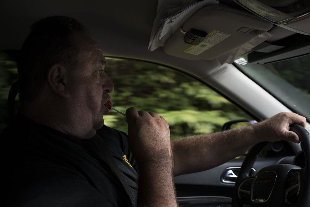 Martin County Sheriff John Kirk enjoys a lollipop while on patrol in Martin County, Kentucky, on July 27, 2018. Due to a dwindling tax base and local budget cuts, the Sheriff's department had faced a round of layoffs in the Spring of 2018 and is expecting a second round in the Fall. Kirk said that if those layoffs were to take place, it would just be him, an office staffer and volunteer deputies for the entire county.