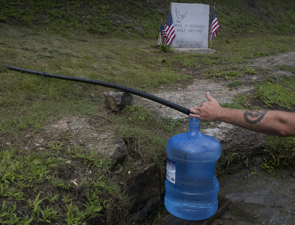 Tim Strong, of Martin County, Ky., fills jugs with spring water off of Highway 119 in Mingo County, West Virginia on August 10, 2018. Many in the county have been reliant on bottled water since 2000, when the wall of a coal slurry pond owned by the Massey Energy company broke and polluted the water supply.