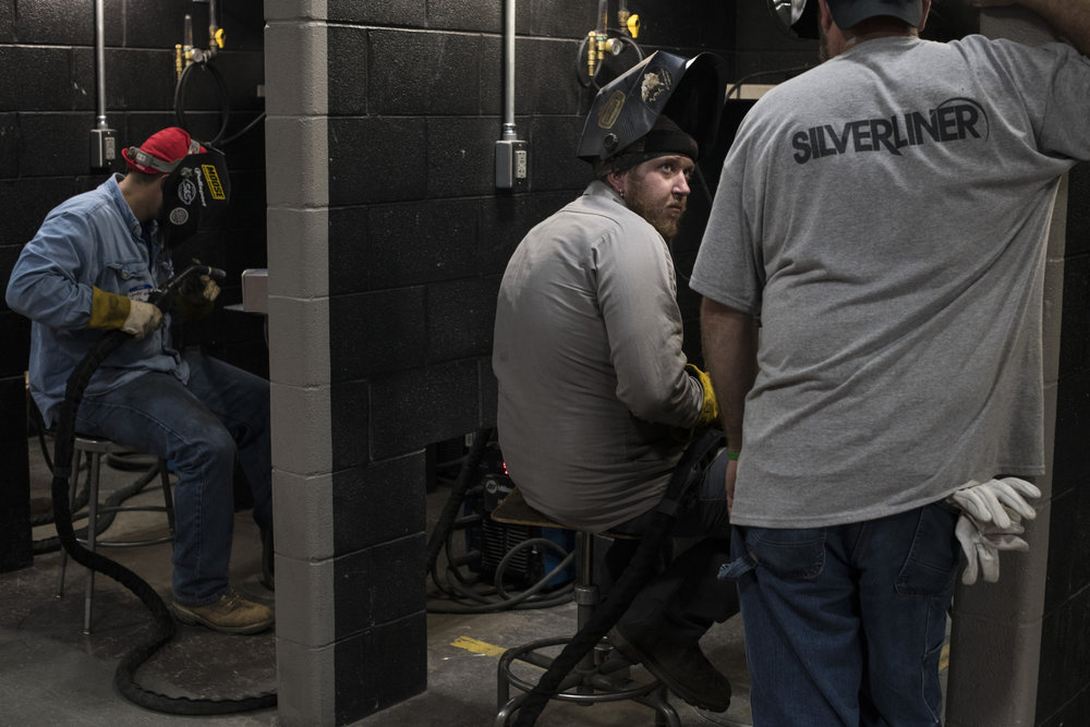 Charles Hinkle, 28, of Inez, Ky., receives feedback on his welding technique by a current trainee during a welding exam at the Big Sandy Community and Technical College in Paintsville, Johnson County, Kentucky, on July 31, 2018. The exam placed successful applicants in a training program for employment with SilverLiner, an aluminum welding company set to open in Pikeville, Ky., at the end of 2018.