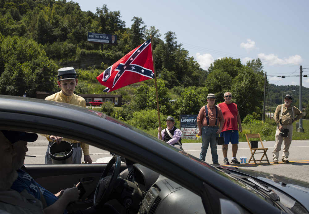 Jacob Ison, 20, collects donations at a highway intersection alongside his fellow Confederate reenactors as they fundraise for the Battle of Middle Creek reenactment in Martin, Floyd County, Kentucky, on August 4, 2018.
