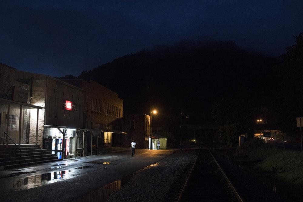 A man walks along Front Street just after dusk in Garrett, Floyd County, Kentucky, on August 1, 2018.